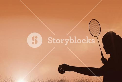 Composite image of female athlete holding a badminton racquet ready to serve