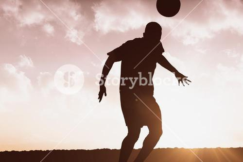 Composite image of football player hitting header