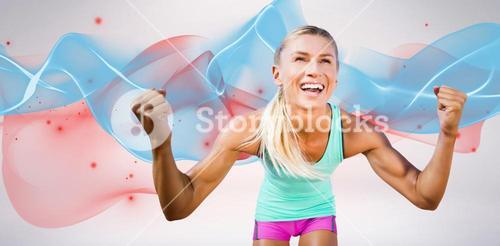 Composite image of portrait of sportswoman smiling and raising arms