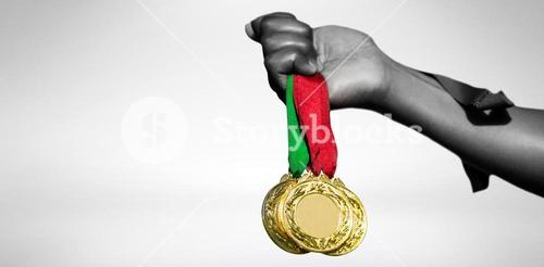 View of hand holding three gold medals