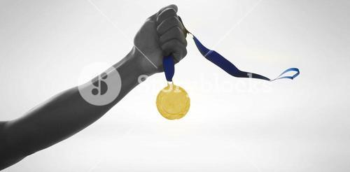 Hand holding a gold medal on white background