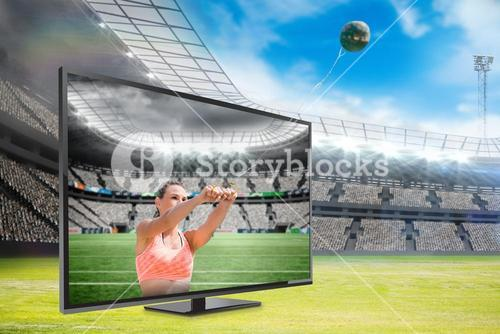 Composite image of portrait of sportswoman practising hammer throw