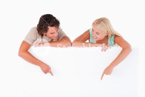 Handsome Man and woman pointing on a whiteboard