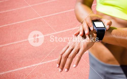 Composite image of close up on a sportswoman wearing a connected watch