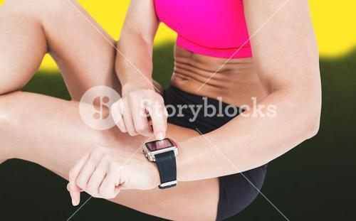 Composite image of female athlete sitting and using her smart watch