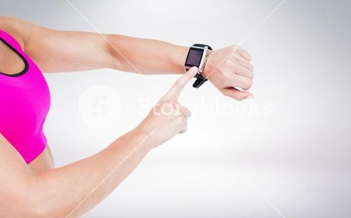 Composite image of female athlete using her smart watch