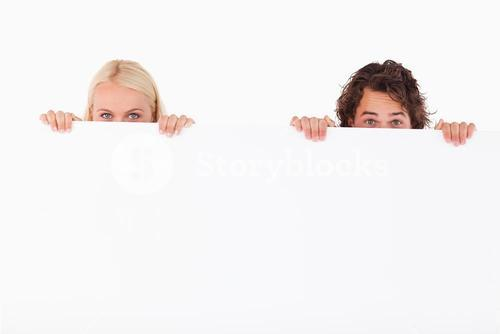 Happy Couple hiding behind a whiteboard
