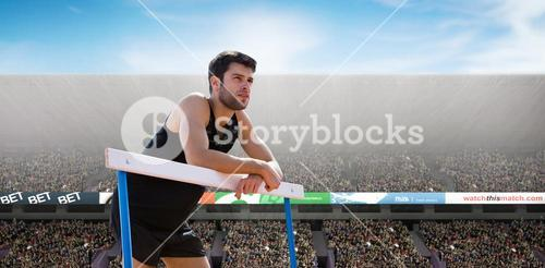 Composite image of athletic man pressed on a hurdle posing
