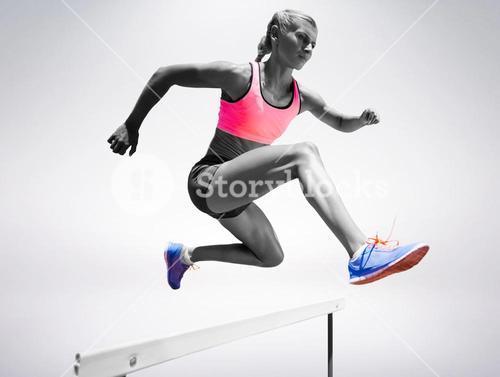 Sporty woman jumping a hurdle