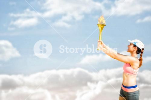 Composite image of sporty woman holding olympic torch