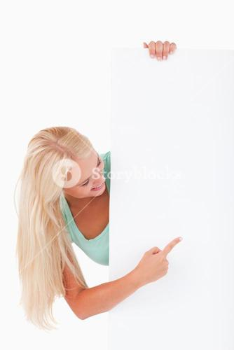 Blondhaired woman pointing at a whiteboard