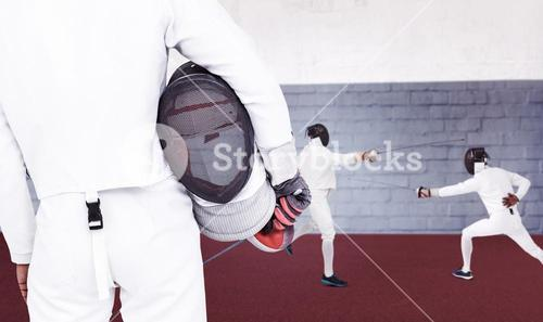 Composite image of rear view of swordsman holding fencing mask and sword