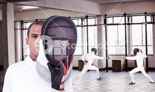 Composite image of swordsman holding fencing mask