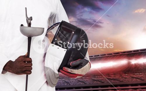 Composite image of mid-section of man standing with fencing mask and sword