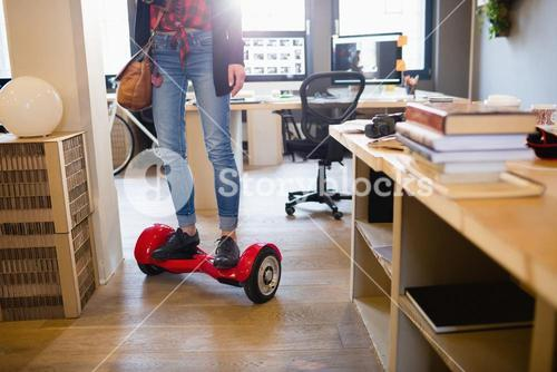 Graphic designer standing on hover board