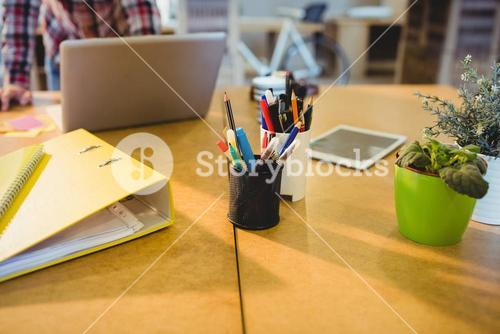 Pen holder with pens and file on table