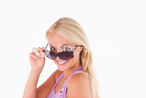 Blond lady peeking over her sunglasses