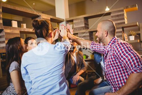 Colleagues giving high five at office