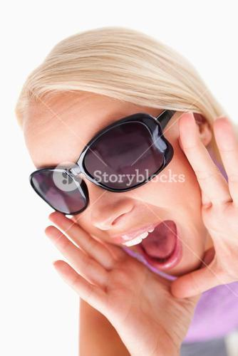 Blond lady with sunglasses in high spirits