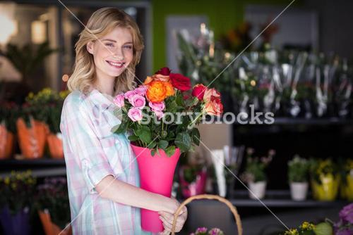 Happy female florist holding flower vase