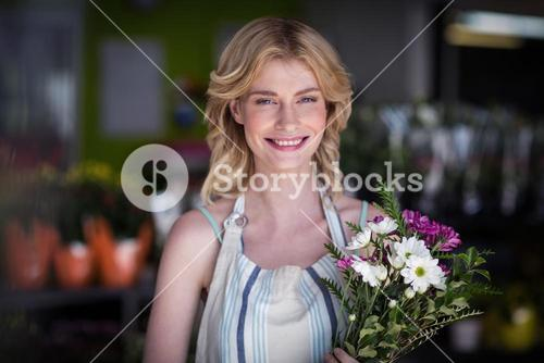 Happy female florist holding bunch of flowers in flower shop