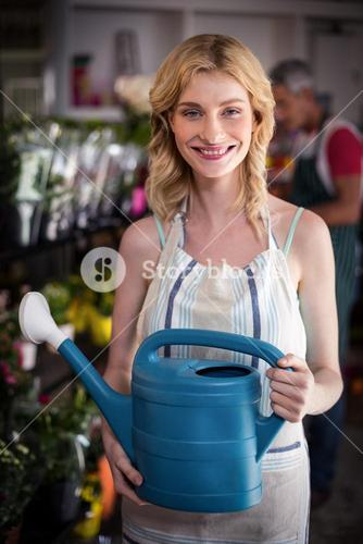 Smiling female florist holding watering can in flower shop