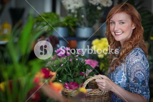 Happy female florist holding basket of flowers