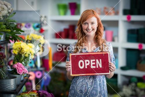 Smiling florists holding open sign placard in flower shop