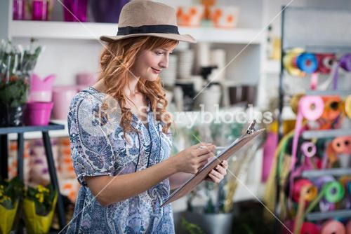 Female florist noting on clipboard