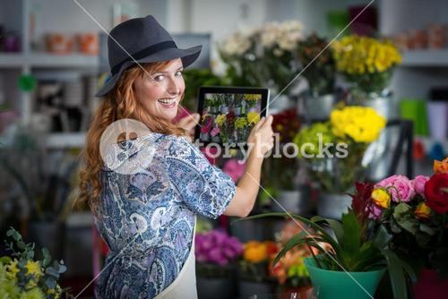 Female florist taking photograph of flowers from digital tablet in flower shop
