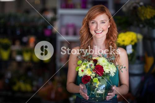 Female florist holding flower vase at flower shop