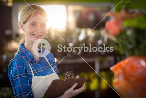 Female florist standing with clipboard