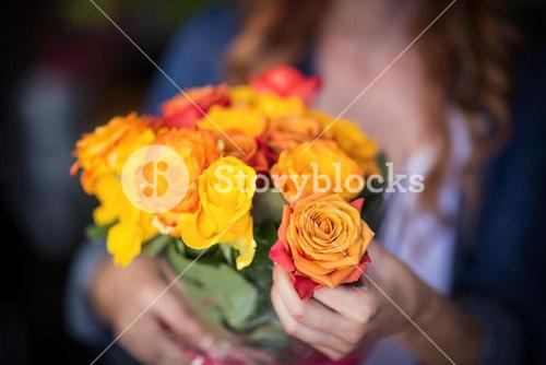 Female florist holding bunch of flowers