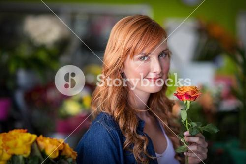 Female florist holding a rose flower