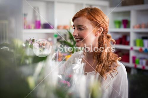 Female florist touching flower bouquet
