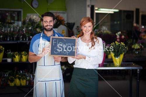 Couple holding slate with flower shop sign