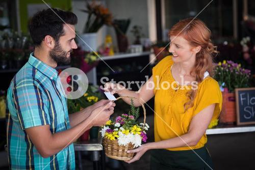 Female florist giving visiting card and flower basket to customer