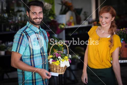 Female florist and customer with flower basket and visiting card