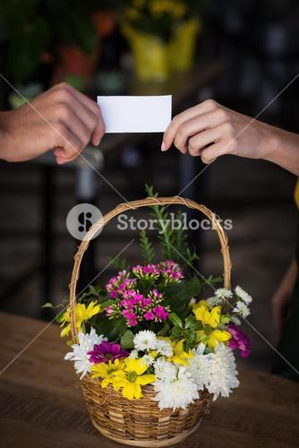 Hand of female florist giving visiting card to customer
