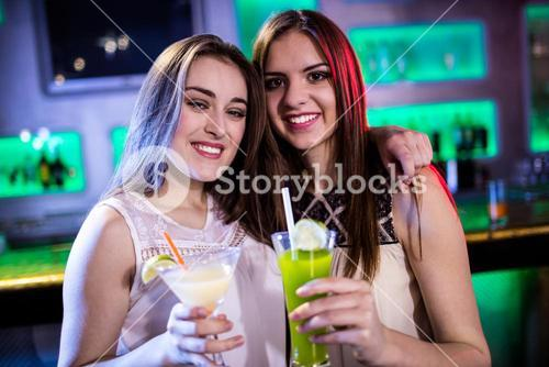 Portrait of beautiful women holding cocktail glasses