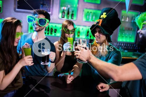 Group of friends toasting beer mugs and drink glasses