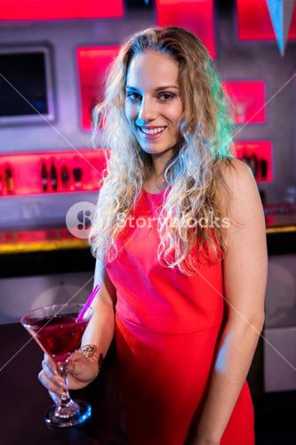 Portrait of beautiful woman holding cocktail glass