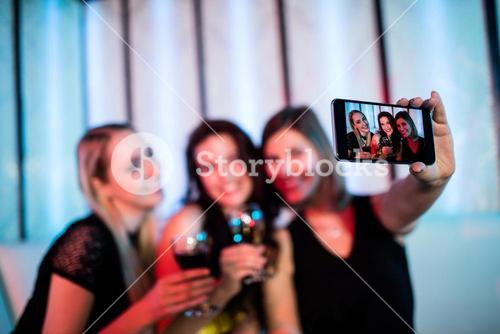 Smiling friends taking a selfie from mobile phone while having wine