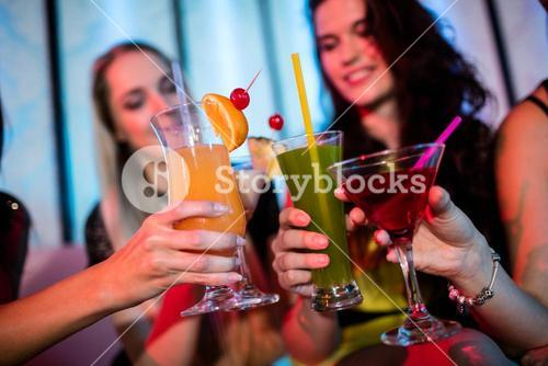Friends sitting on sofa and toasting a glasses of mocktail