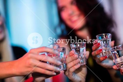 Group of friends toasting tequila shot glasses