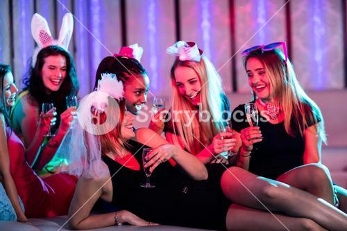 Group of women interacting while having a glass of champagne
