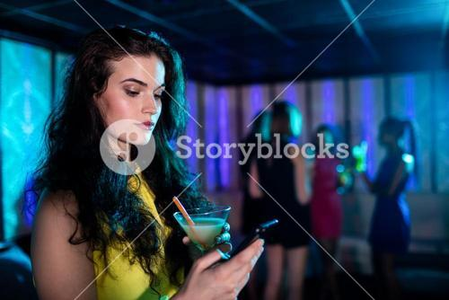 Beautiful woman typing a text message while having cocktail