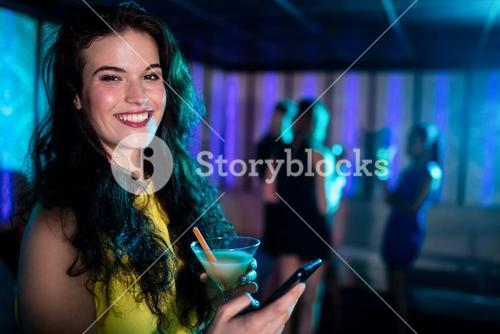 Beautiful woman using mobile phone while having cocktail