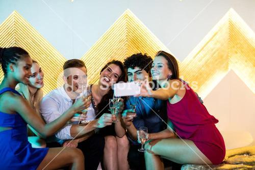 Group of friends taking selfie while having glasses of champagne