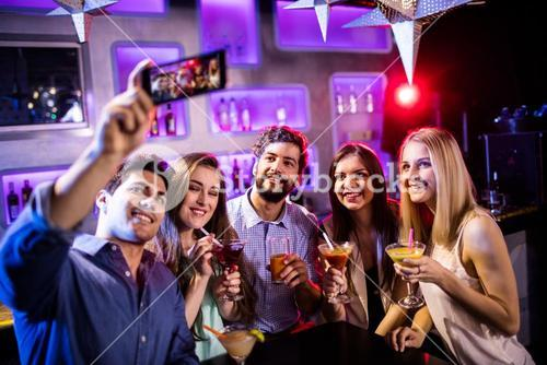 Group of friends taking selfie while having glasses of cocktail